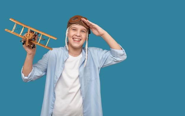Uma criança com um chapéu de piloto e um brinquedo de avião