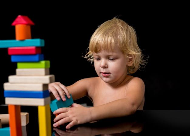 Uma criança com um distúrbio do espectro do autismo constrói uma casa a partir de um construtor de madeira