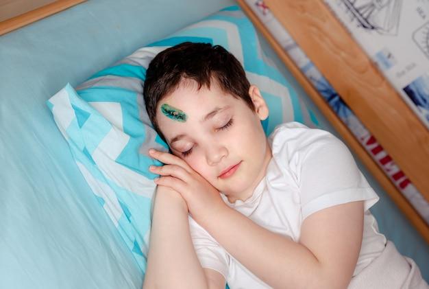 Uma criança com um ferimento na cabeça está dormindo em uma cama no quarto dele. o cirurgião costurou a pele na testa