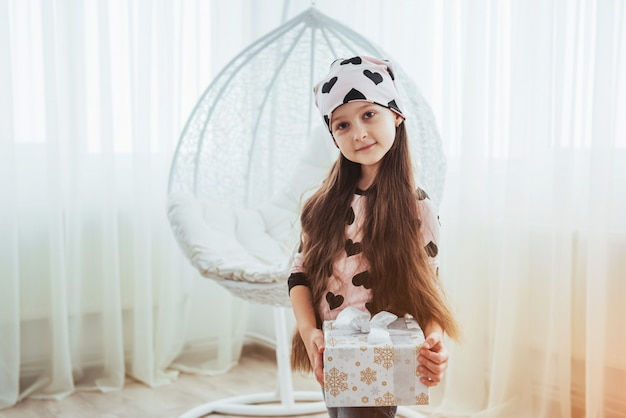 Uma criança com um presente em um estúdio bonito e brilhante.