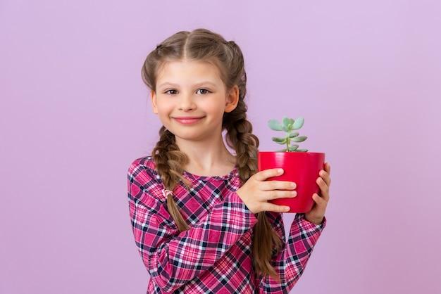 Uma criança com um vestido roxo xadrez segura uma planta verde em um vaso vermelho.