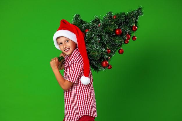 Uma criança com uma árvore de natal decorada
