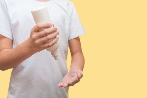 Uma criança com uma camiseta branca em uma parede amarela trata suas mãos com um spray de um frasco contra o vírus
