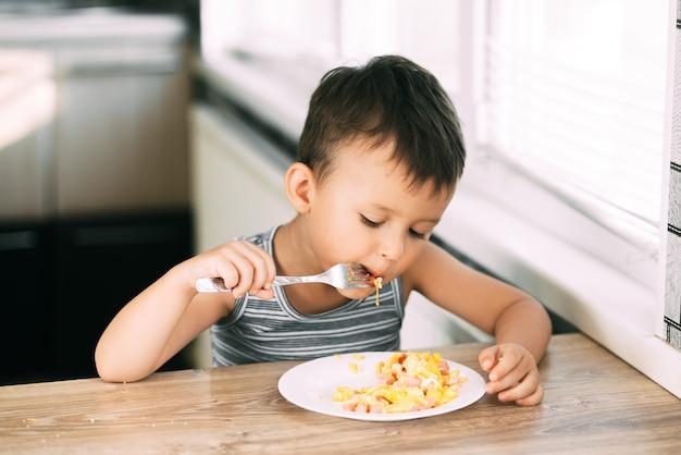 Uma criança com uma camiseta na cozinha comendo uma omelete com salsicha e tomate com um garfo