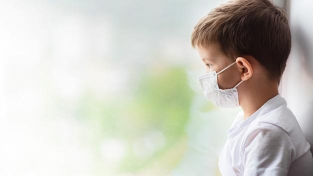 Uma criança com uma máscara médica está sentada em casa em quarentena por causa do coronavírus e da cobertura 19 e olha pela janela.