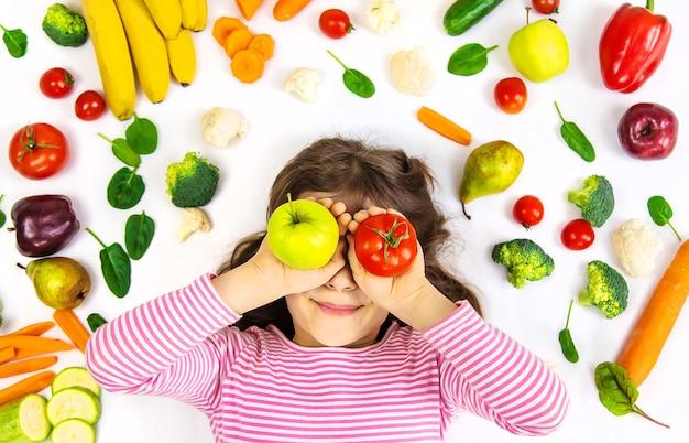 Uma criança com vegetais e frutas nas mãos