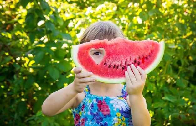Uma criança come melancia. foco seletivo. comida