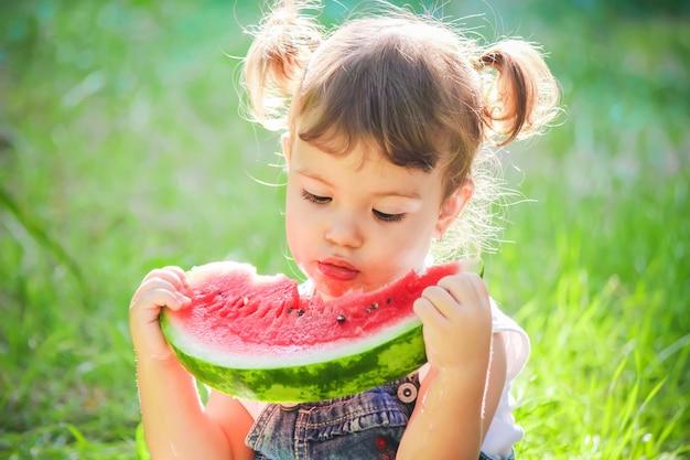 Uma criança come melancia. foco seletivo.