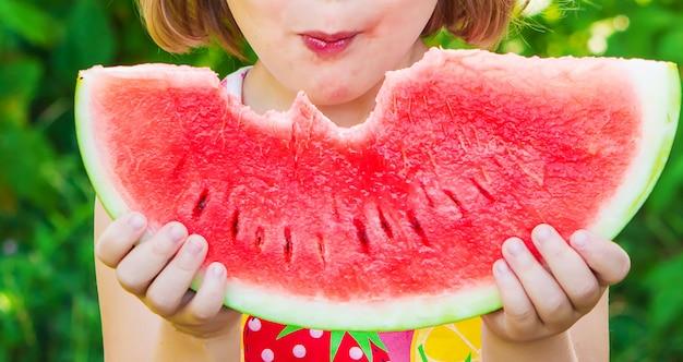 Uma criança come melancia. foto. comida