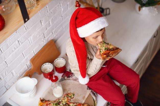 Uma criança come pizza na cozinha