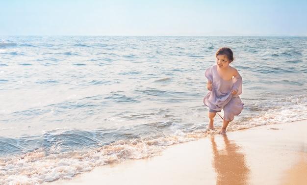 Uma criança corre das ondas na areia da praia nas férias