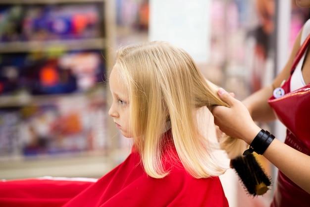 Uma criança corta o cabelo em um salão de beleza.