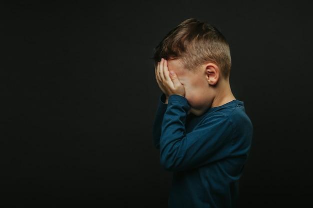 Uma criança cuja depressão com as mãos fechadas