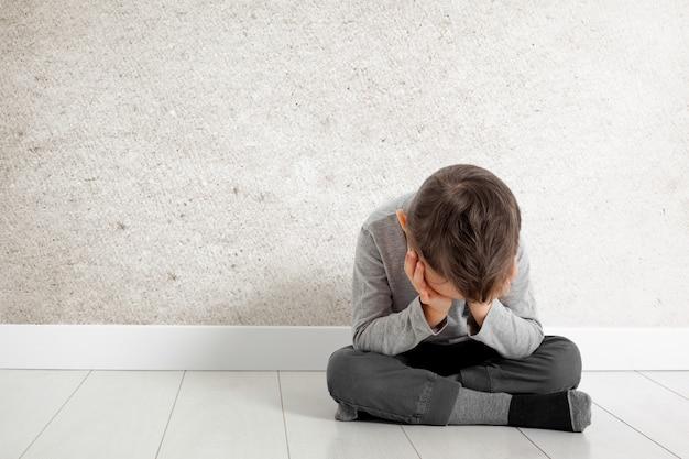 Uma criança cuja depressão está sentada no chão