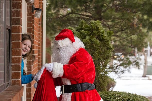 Uma criança dando uma caixa de presente para o papai noel comemora o natal