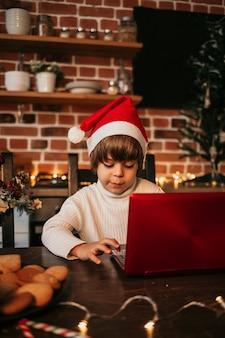 Uma criança de ano novo com um suéter branco e um chapéu vermelho de ano novo está sentada a uma mesa e digitando uma carta em um laptop vermelho