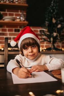 Uma criança de ano novo está sentada à mesa com um chapéu vermelho de ano novo e escrevendo em um pedaço de papel