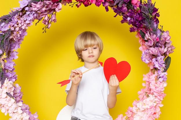 Uma criança de blodne vista frontal em t-shirt branca segurando coração forma sentado sobre a flor fez ficar no espaço amarelo