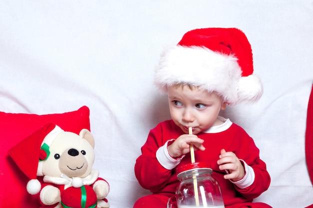 Uma criança de boné vermelho come biscoitos e leite. natal um bebê em um boné vermelho. feriados de ano novo e natal