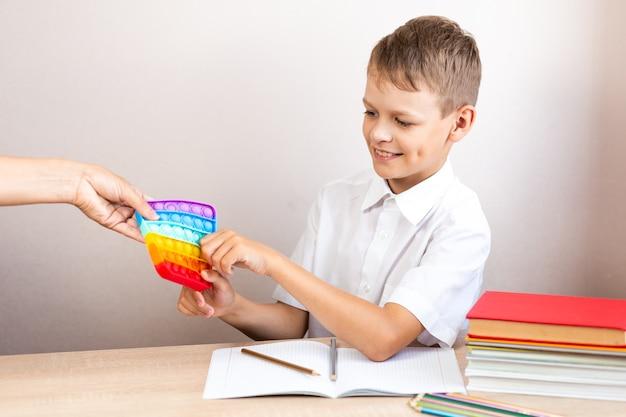 Uma criança de camisa branca se senta a uma mesa e pega uma bolha eterna das mãos de uma mulher para brincar com um brinquedo, não para estudar