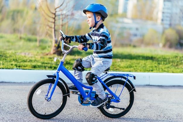 Uma criança de capacete e proteção em um passeio de bicicleta na natureza na primavera