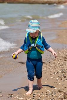 Uma criança de colete de natação e bola nas mãos caminha ao longo da água ao longo da praia.