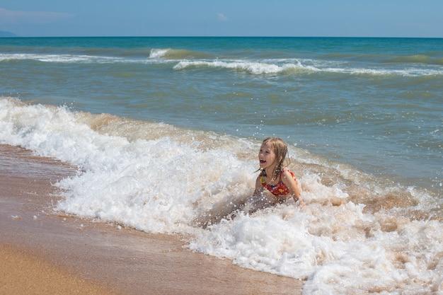Uma criança de maiô ri, chapinhando nas ondas do mar. férias de verão no mar.
