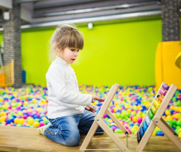 Uma criança de suéter branco e jeans na sala de jogos brinca com um ábaco de madeira