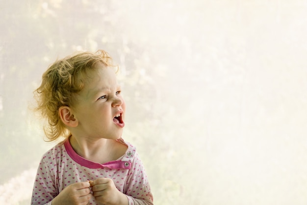 Uma criança de três anos fazendo caretas emocionalmente