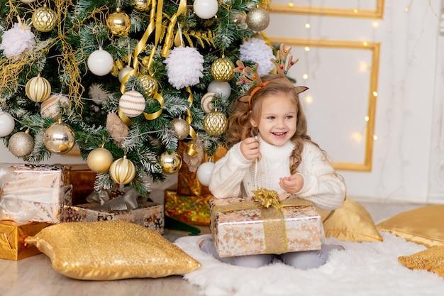 Uma criança desembrulha um presente de ano novo perto de uma árvore de natal com uma decoração dourada em casa