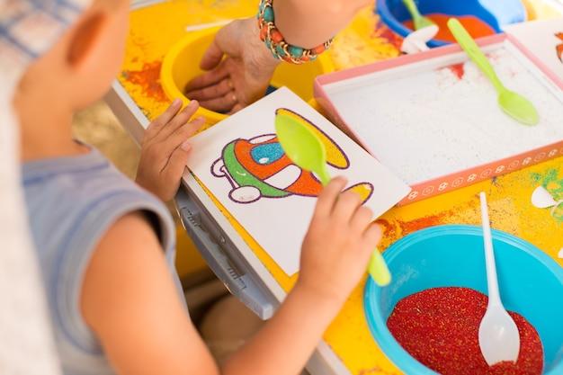 Uma criança desenha com imagens coloridas de areia. personagens de desenhos animados.