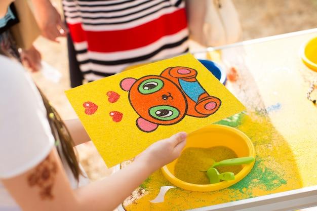 Uma criança desenha com imagens de areia coloridas. personagens de desenhos animados.