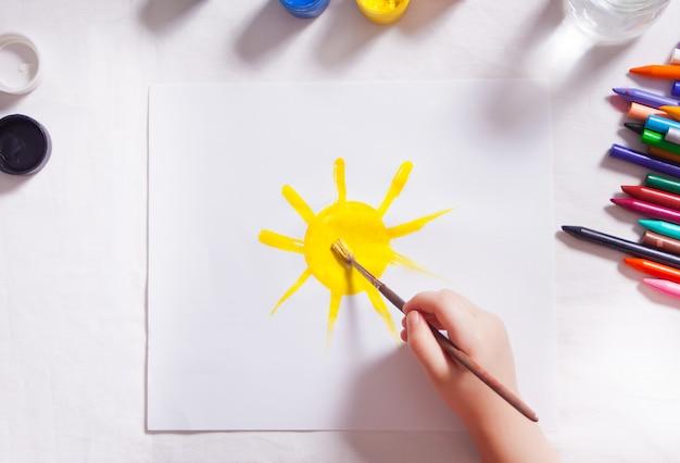 Uma criança desenha sol com tintas coloridas no papel.