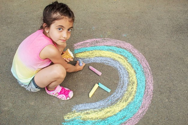 Uma criança desenha um arco-íris no asfalto. foco seletivo. criança.