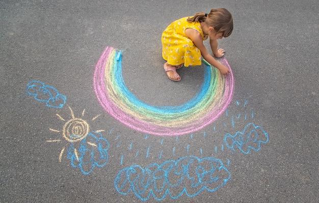 Uma criança desenha um arco-íris no asfalto. foco seletivo.