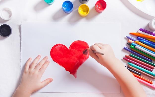 Uma criança desenha um coração vermelho com tintas coloridas no papel.