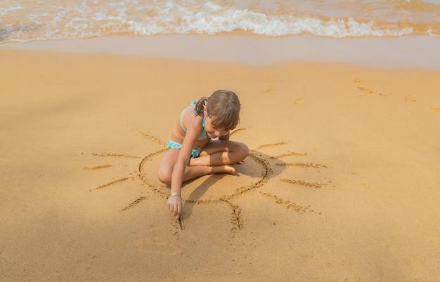 Uma criança desenha um sol na praia.