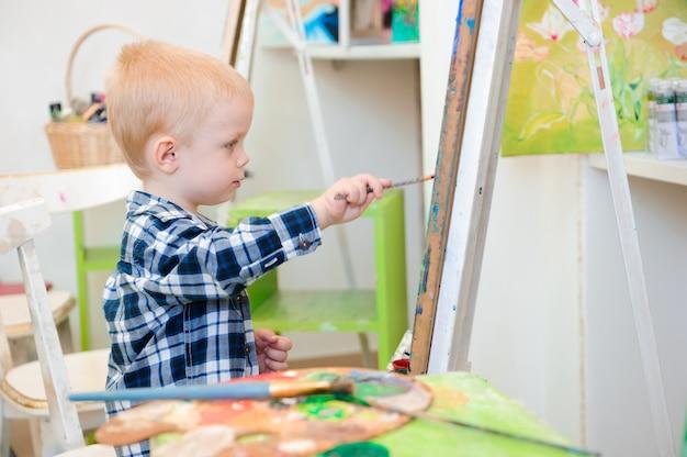 Uma criança desenha uma pintura na aula de arte
