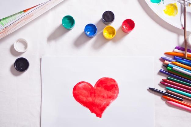 Uma criança desenhando coração vermelho com tintas coloridas no papel.