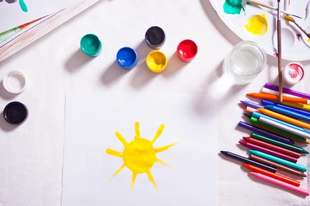 Uma criança desenhando o sol com tintas coloridas no papel.