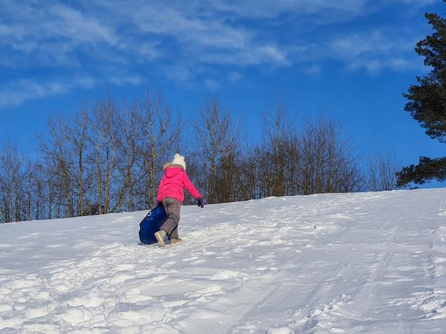 Uma criança desliza em um escorregador de neve.