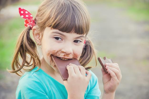Uma criança doce come chocolate. foco seletivo.