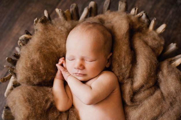 Uma criança dormindo com as mãos sob as bochechas em uma sessão de fotos de recém-nascidos