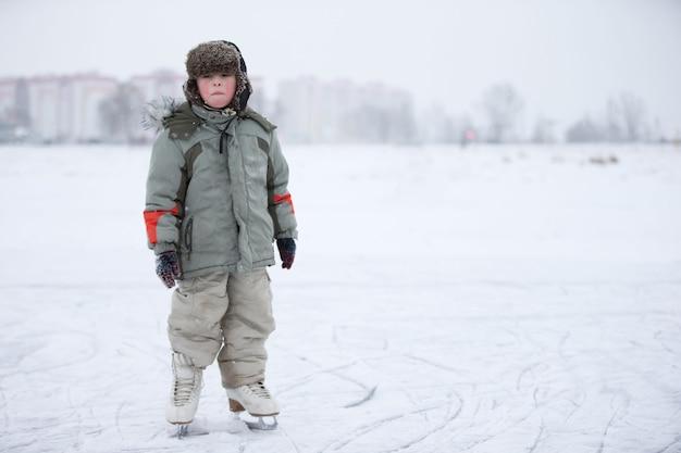 Uma criança é um menino de patins em um lago nevado aprenda a andar