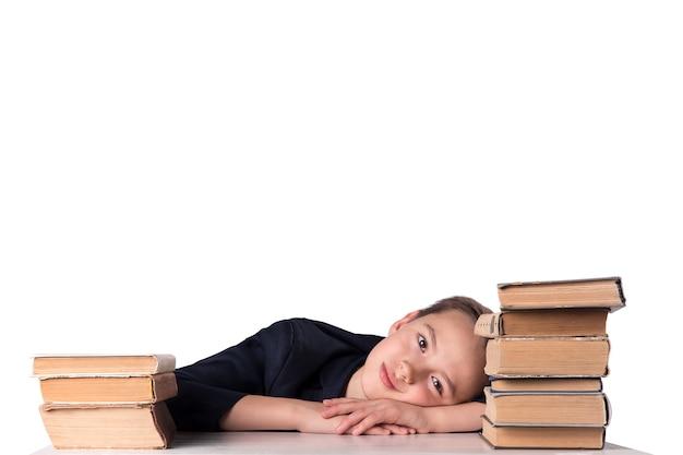 Uma criança em idade escolar faz o dever de casa. o menino faz sua lição de casa em sua mesa em casa. o aluno está entediado com a lição. de volta à escola.