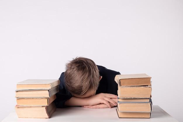 Uma criança em idade escolar faz o dever de casa. o menino faz sua lição de casa em sua mesa em casa. o aluno está entediado com a lição. o menino adormeceu durante o dever de casa. adorável aluno da primeira série.