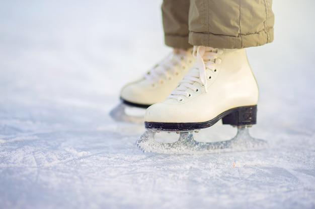 Uma criança em patins fica no gelo, patins closeup.