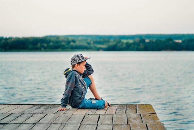 Uma criança em roupas elegantes estão posando em uma sessão de fotos na ponte do lago