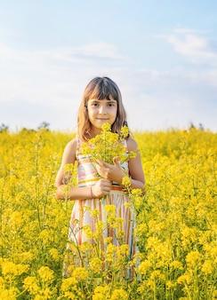 Uma criança em um campo amarelo, flores de mostarda