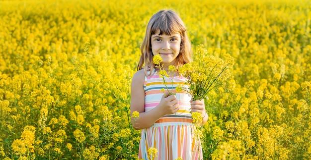 Uma criança em um campo amarelo, mostarda floresce